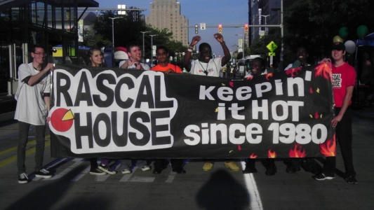 rascal house employees holding up banner that reads 'keepin it hot since 1980'